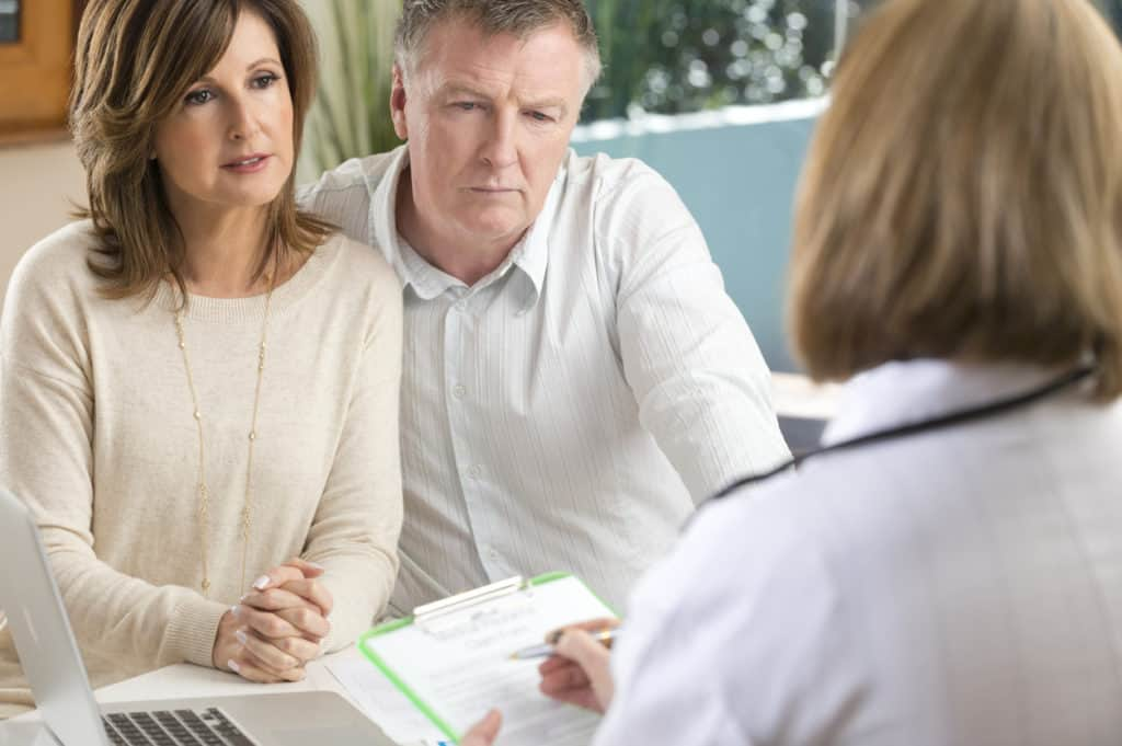 Doctor filling out form with worried mature couple. Shallow focus